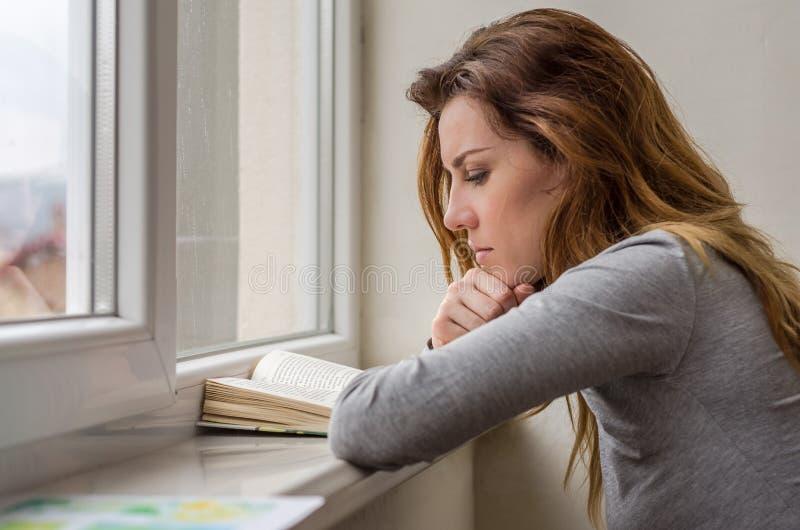 Giovane studentessa affascinante, con capelli lunghi, tristi al libro di lettura della finestra con le lezioni fotografia stock libera da diritti