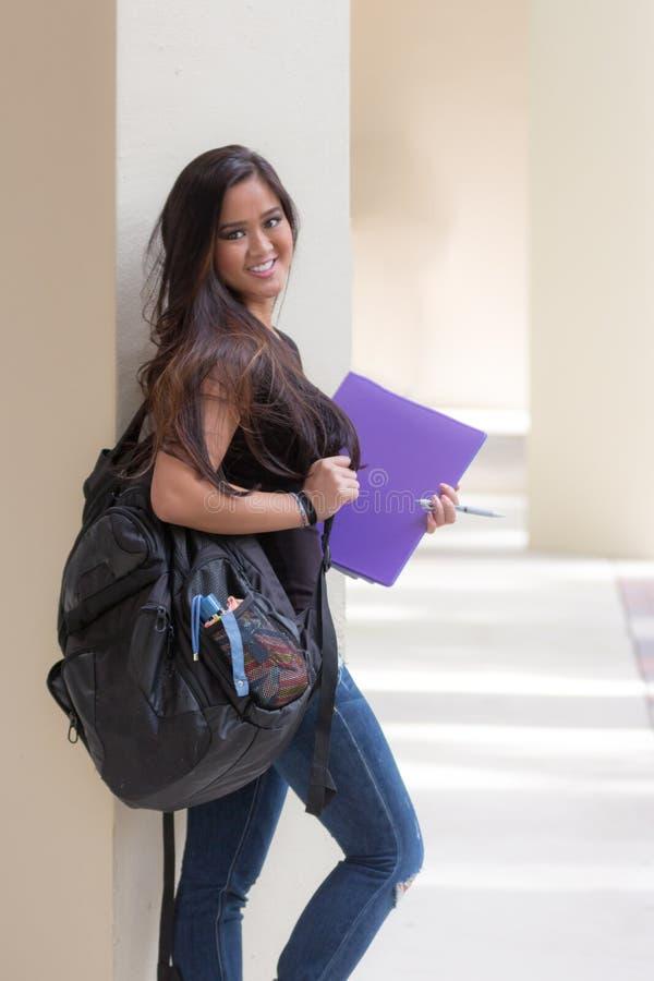 Giovane studentessa asiatica attraente con lo zaino ed il raccoglitore sopra immagine stock libera da diritti