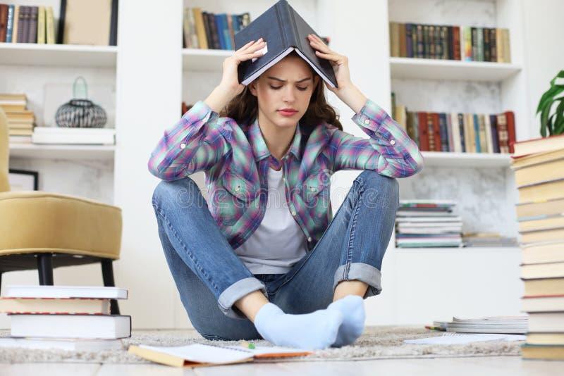Giovane studentessa che studia a casa, sedendosi sul pavimento contro l'interno domestico accogliente, circondato con il mucchio  fotografia stock