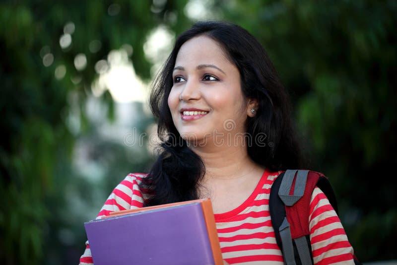 Giovane studentessa felice alla città universitaria dell'istituto universitario immagini stock libere da diritti