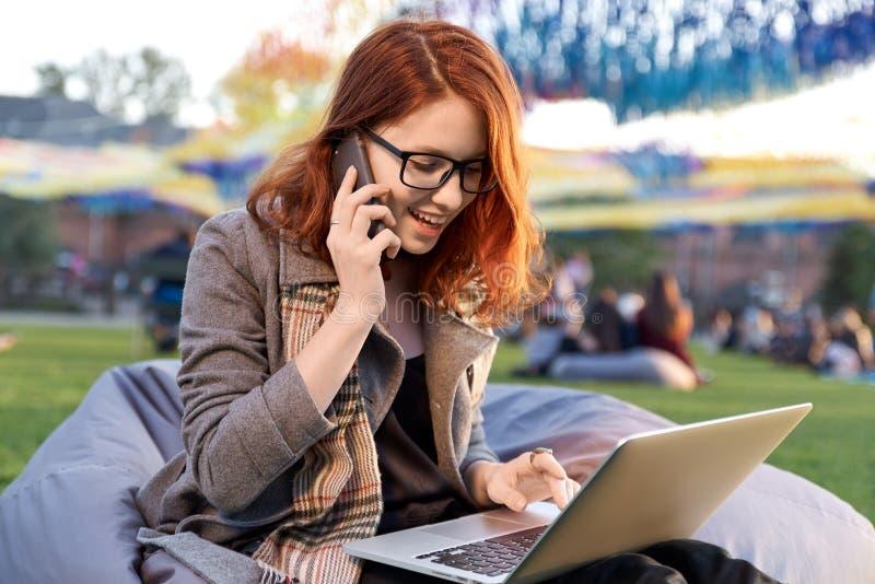 Giovane studentessa sorridente che per mezzo del computer portatile portatile per la preparazione agli esami all'università, keyb immagini stock