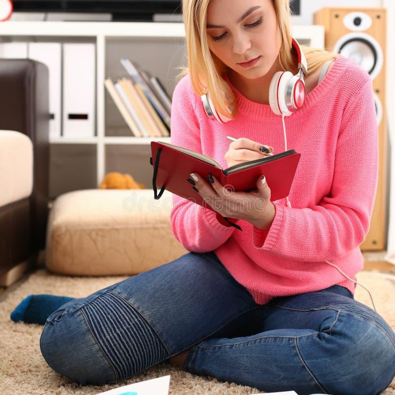 Giovane studio grazioso della donna al libro della tenuta del salone in armi immagini stock