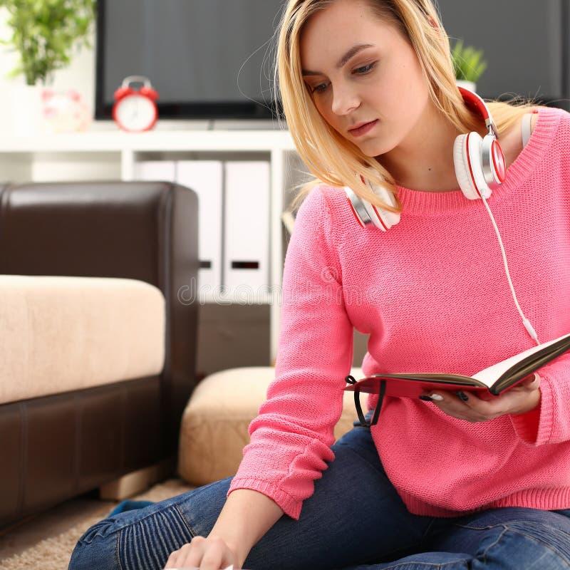 Giovane studio grazioso della donna al libro della tenuta del salone in armi fotografie stock