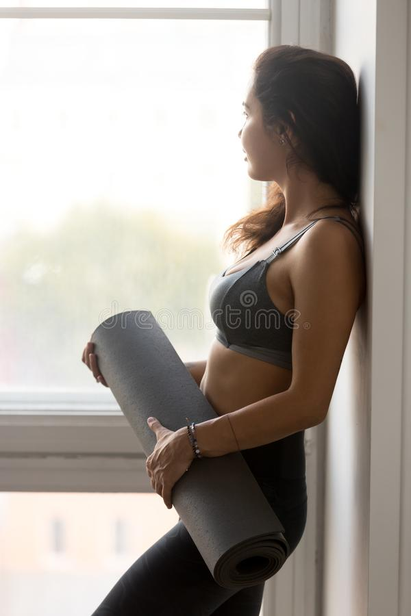 Giovane stuoia sportiva di forma fisica della tenuta della donna, istruttore di yoga immagini stock libere da diritti