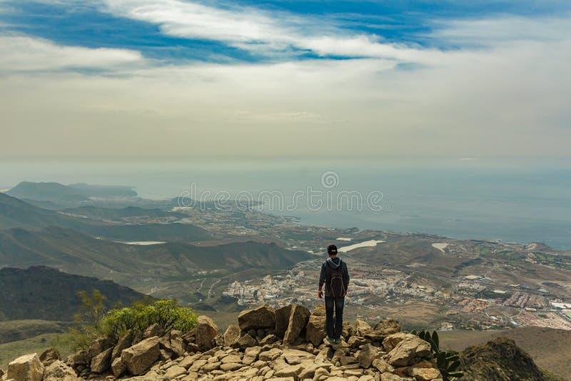 Giovane sull'orlo di una scogliera rocciosa al giorno soleggiato Chiaro cielo blu ed alcune nuvole lungo l'orizzonte Inseguimento fotografia stock