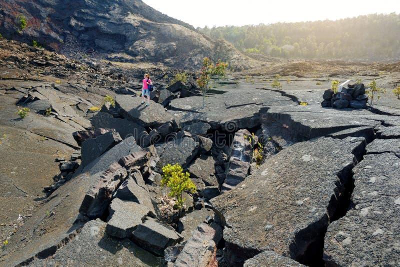 Giovane superficie d'esplorazione turistica femminile del cratere del vulcano di Kilauea Iki con la roccia di sbriciolatura della immagini stock