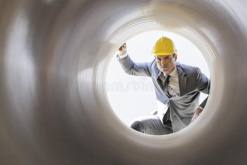 Giovane supervisore maschio che esamina grande tubo al cantiere immagini stock libere da diritti