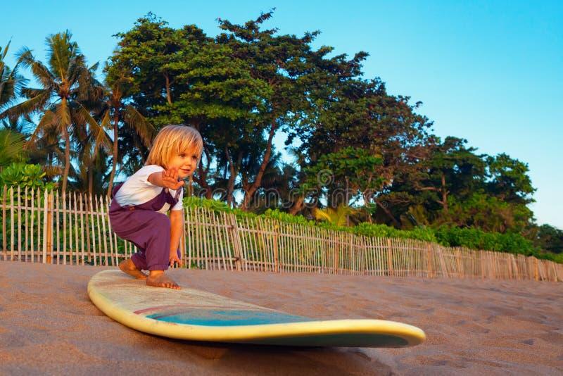 Giovane supporto del surfista sul surf con divertimento sulla spiaggia di tramonto immagini stock