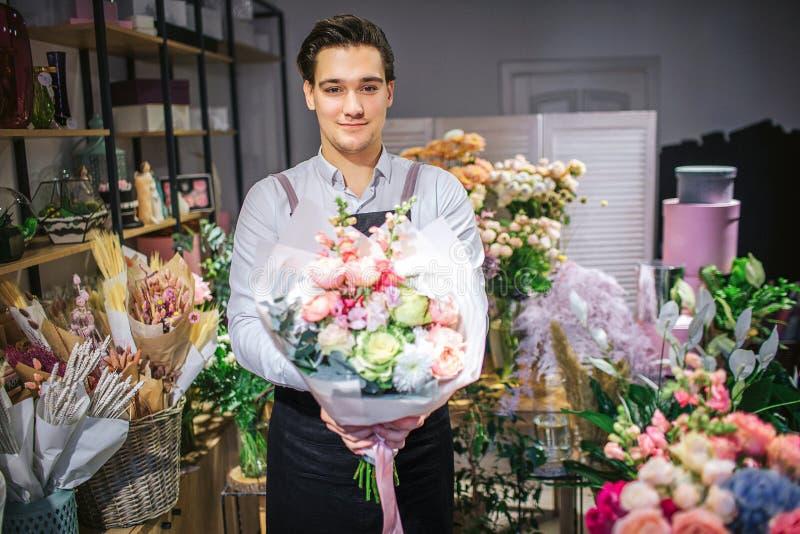 Giovane supporto maschio bello del fiorista e considerare macchina fotografica Tiene il mazzo dei fiori in mani Interno del suppo immagine stock