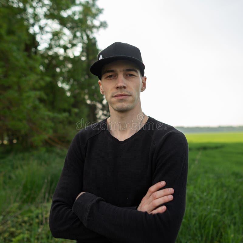 Giovane sveglio moderno in un berretto nero alla moda in una camicia nera alla moda che posa fra l'erba verde in un campo fuori d fotografia stock