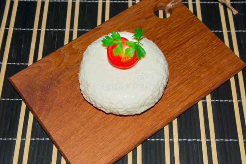 Giovane tagliere del formaggio della quercia con i pomodori ed il prezzemolo Mozarella per le pizze e le insalate fotografie stock libere da diritti