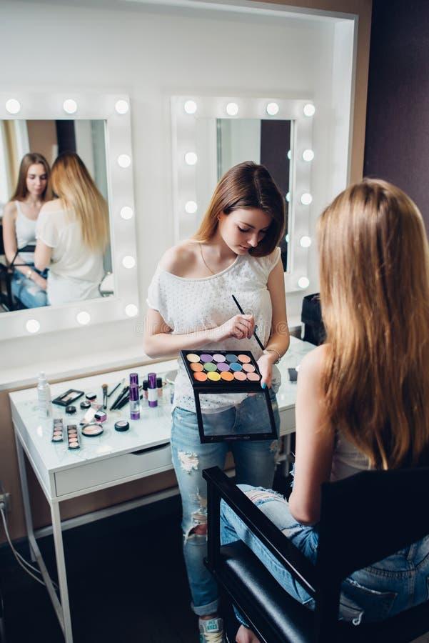 Giovane tavolozza professionale della tenuta del visagiste che applica ombretto al modello femminile caucasico nel negozio di bel fotografia stock