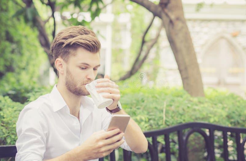 Giovane tazza di caffè bella della bevanda dell'uomo di affari facendo uso del telefono cellulare nel parco immagini stock libere da diritti