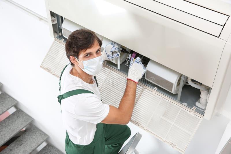 Giovane tecnico maschio che ripara condizionatore d'aria immagini stock