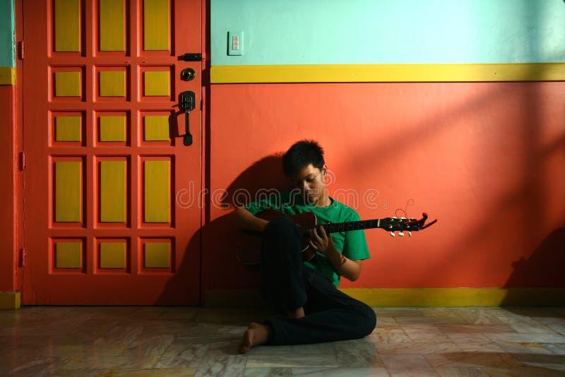 Giovane teenager asiatico giocando la chitarra in un salone fotografie stock