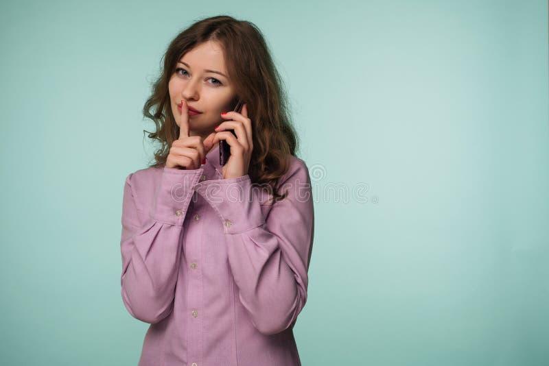 Giovane telefono cellulare attraente della tenuta della donna e mostrare gesto di silenzio isolato su un fondo immagine stock