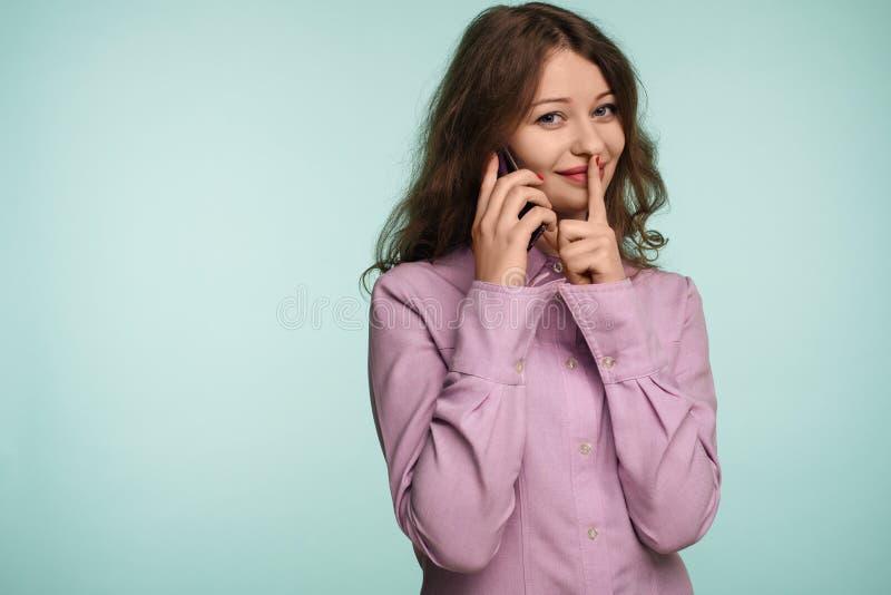 Giovane telefono cellulare attraente della tenuta della donna e mostrare gesto di silenzio su un fondo fotografia stock