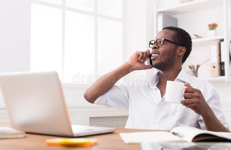 Giovane telefono cellulare nero di chiamata dell'uomo d'affari in ufficio bianco moderno immagini stock