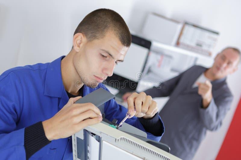 Giovane televisione maschio di In Overall Checking dell'elettricista fotografie stock libere da diritti