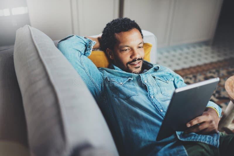 Giovane tempo africano barbuto di freddo di spesa dell'uomo in sofà ed esaminare l'appartamento moderno della compressa Concetto  immagine stock