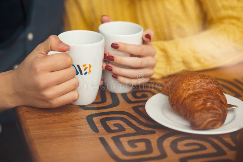 Giovane tenersi per mano e tazze delle coppie con caffè immagine stock