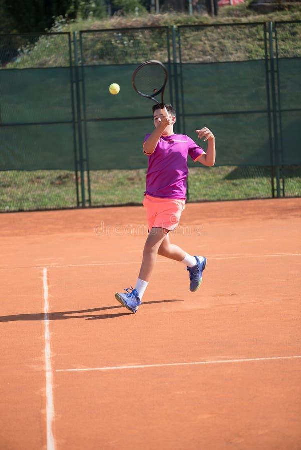 Giovane tennis che colpisce la palla immagini stock libere da diritti