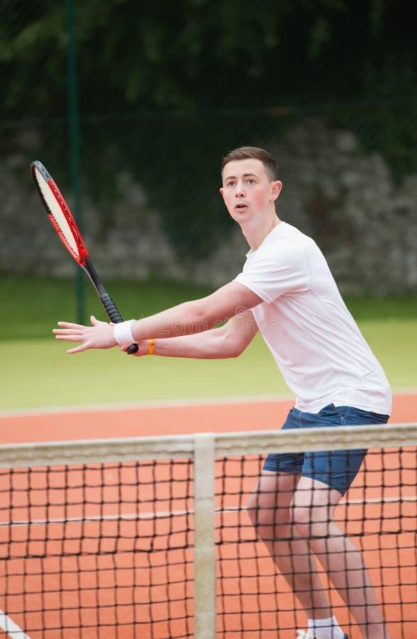 Giovane tennis che colpisce palla fotografia stock libera da diritti