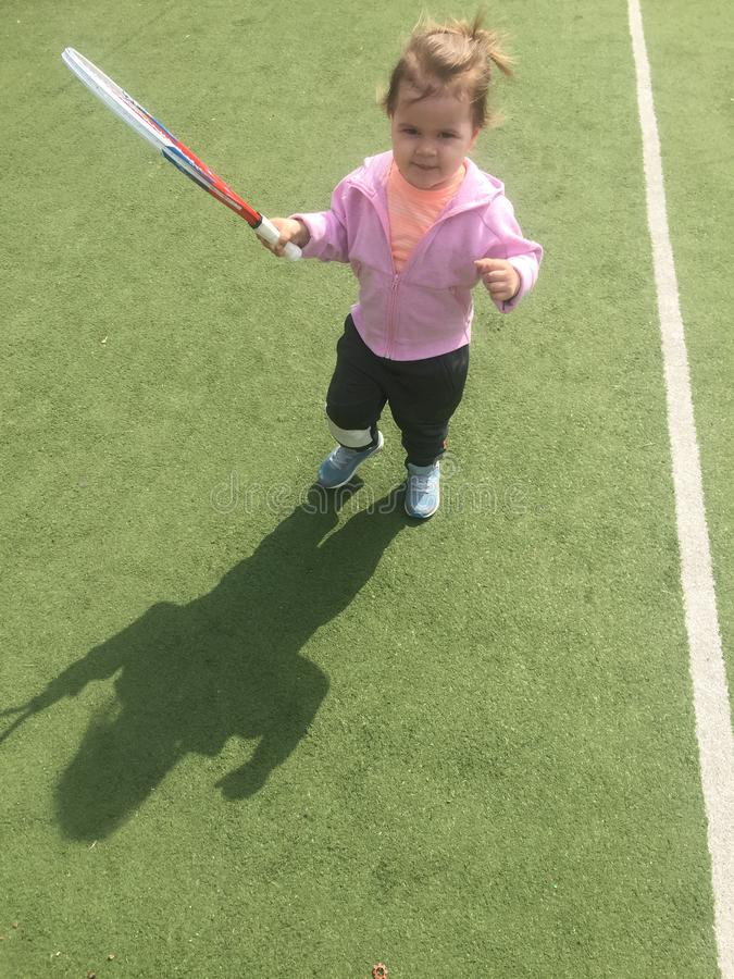 Giovane tennis grazioso con una racchetta su un campo da tennis sull'erba di tennis, addestramento del tennis dei bambini immagini stock libere da diritti