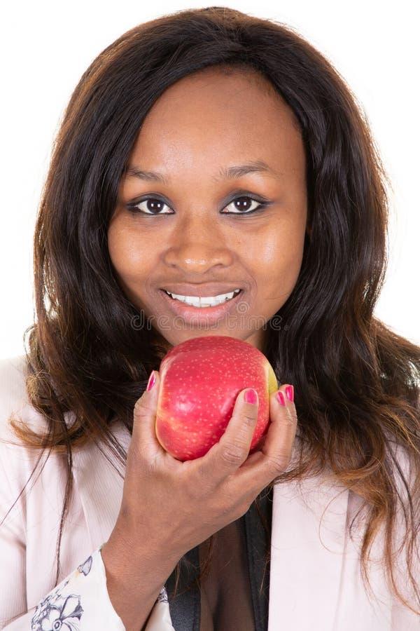 Giovane tenuta afroamericana graziosa felice della donna che mangia mela rossa immagine stock libera da diritti