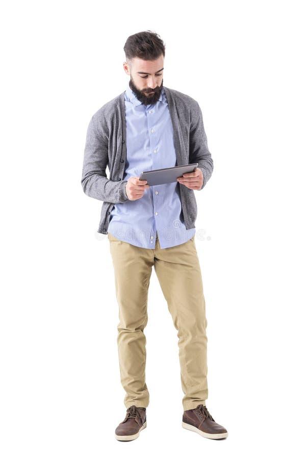 Giovane tenuta barbuta adulta dei pantaloni a vita bassa e guardare al computer della compressa fotografia stock libera da diritti