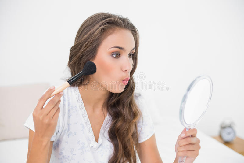 Giovane tenuta castana attraente una spazzola e uno specchio immagine stock