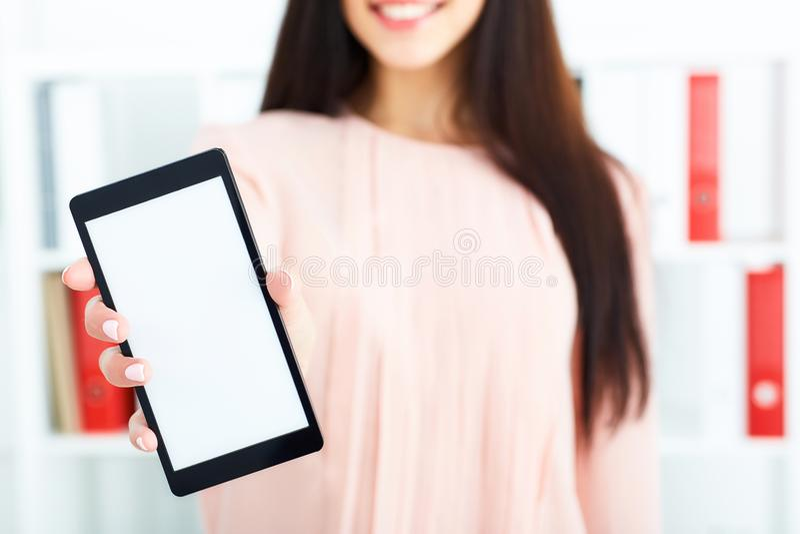 Giovane tenuta castana uno smartphone con lo schermo in bianco Affare, mercato dei cambi, offerta di lavoro, ricerca di analisi d immagini stock libere da diritti