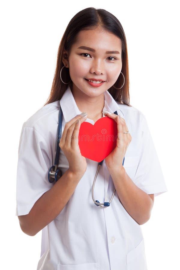Giovane tenuta femminile asiatica di medico un cuore e un sorriso rossi immagine stock libera da diritti