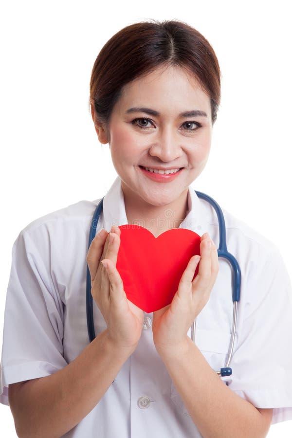 Giovane tenuta femminile asiatica di medico un cuore e un sorriso rossi immagini stock libere da diritti