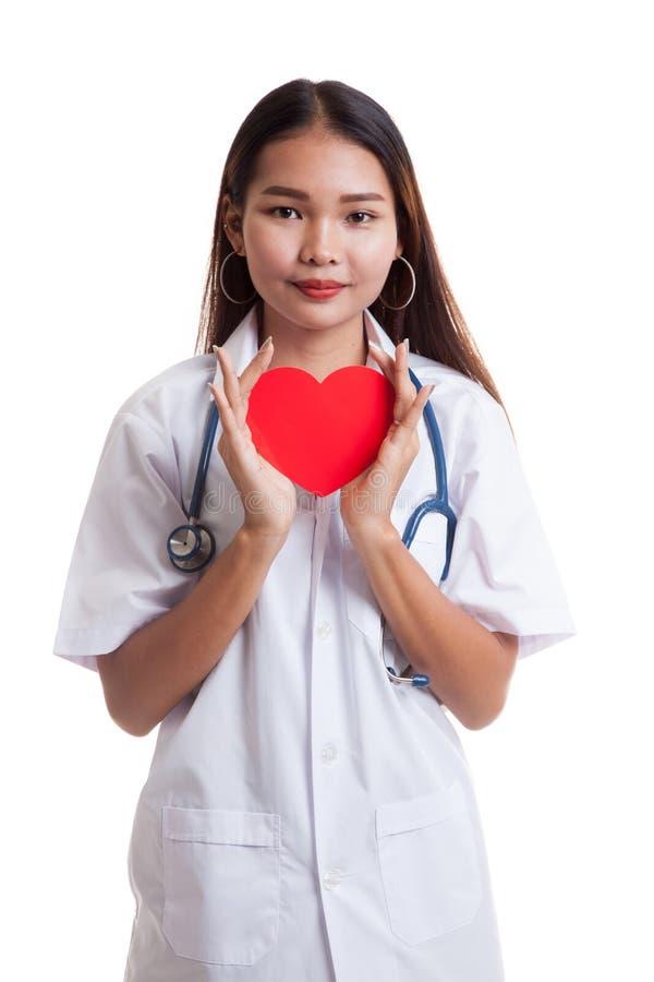 Giovane tenuta femminile asiatica di medico un cuore rosso fotografia stock libera da diritti