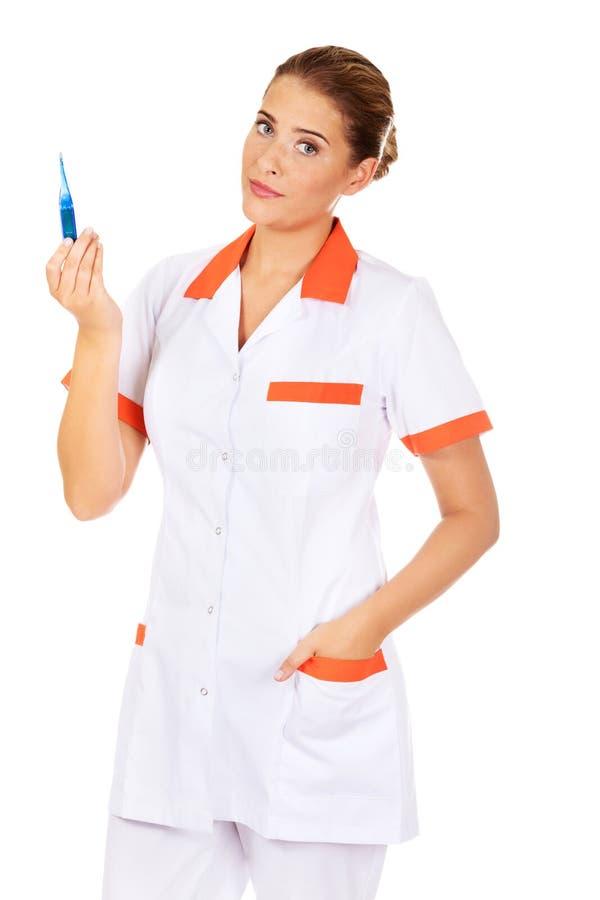 Giovane termometro femminile della tenuta dell'infermiere o di medico immagine stock libera da diritti