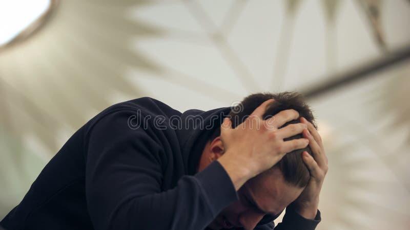 Giovane testa di tenuta maschio, soffrente dai postumi di una sbornia dopo il partito di notte, vomitante immagini stock libere da diritti