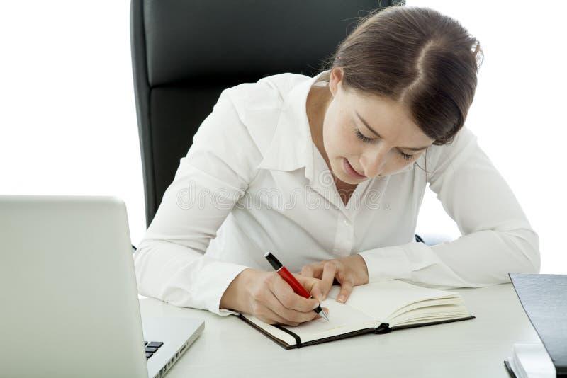 Giovane testo di scrittura della donna di affari del brunette in libro immagini stock libere da diritti