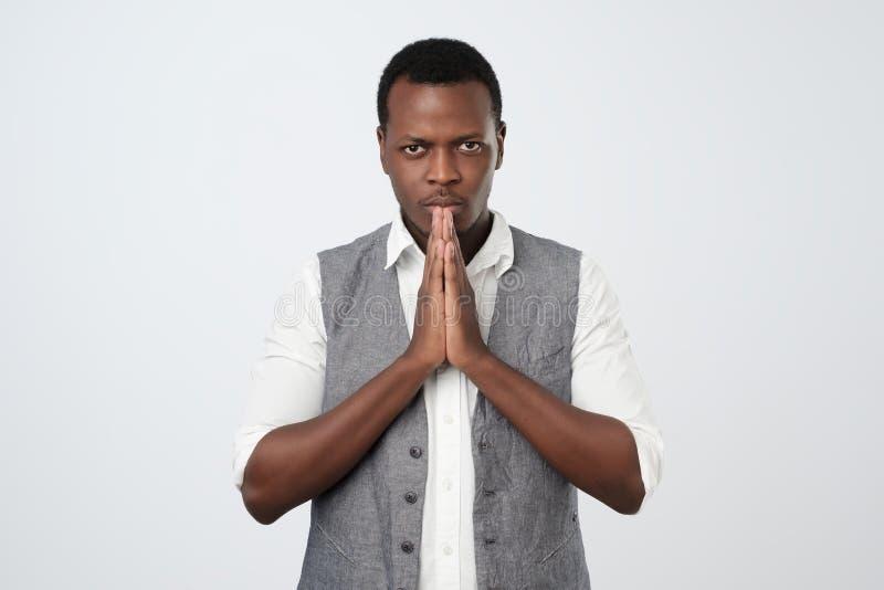 Giovane tipo africano che chiede un favore Coprami prego sul lavoro fotografia stock libera da diritti
