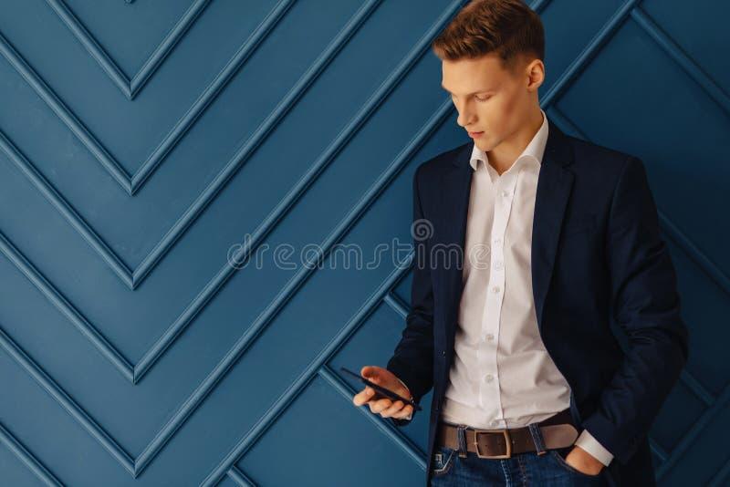 Giovane tipo alla moda con un telefono, giovane uomo d'affari, free lance fotografia stock
