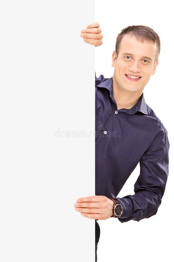 Giovane tipo allegro che posa dietro il pannello fotografia stock