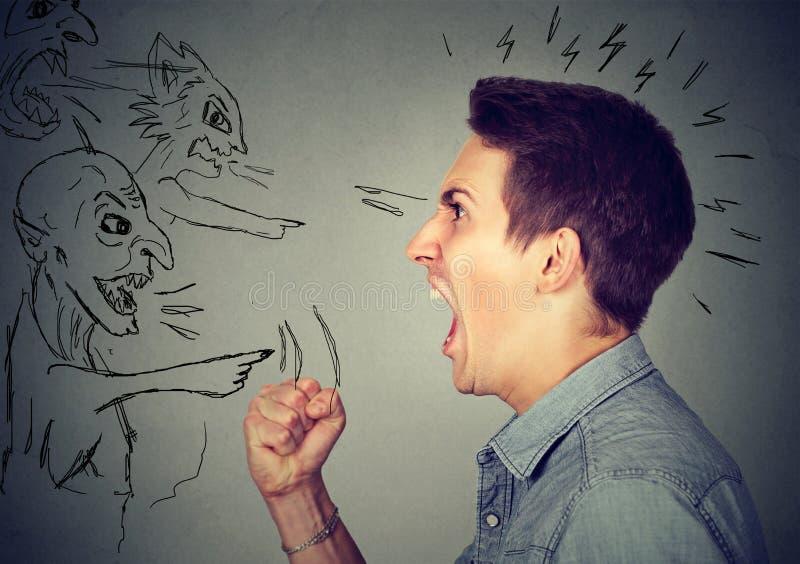 Giovane tipo arrabbiato ed uomini diabolici che gridano ad a vicenda immagini stock