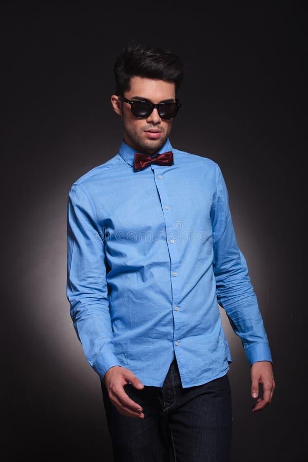 Giovane tipo bello che cammina intorno mentre indossando gli occhiali da sole fotografia stock