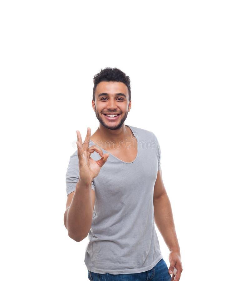 Giovane tipo bello dell'uomo della tenuta di Okey di gesto di sorriso felice casuale del segno fotografia stock libera da diritti
