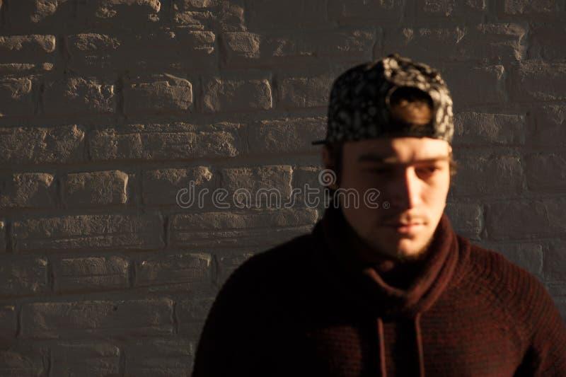 Giovane tipo bello in un berretto da baseball contro il fondo del muro di mattoni immagine stock