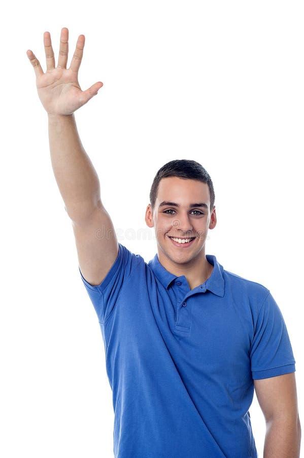 Giovane tipo che ondeggia ciao al suo amico immagine stock libera da diritti