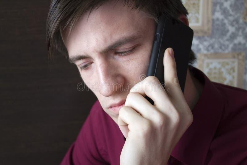 Giovane tipo che parla sul telefono, guardante giù fotografia stock
