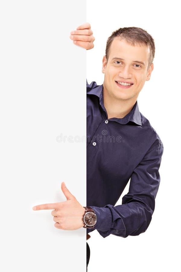 Giovane tipo che posa dietro un pannello immagini stock libere da diritti