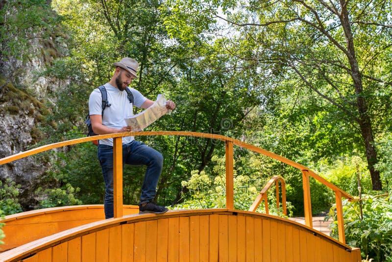 Giovane tipo che un viaggiatore in un cappello con uno zaino sta su un ponte, studia l'itinerario, cerca la strada sulla mappa fotografia stock