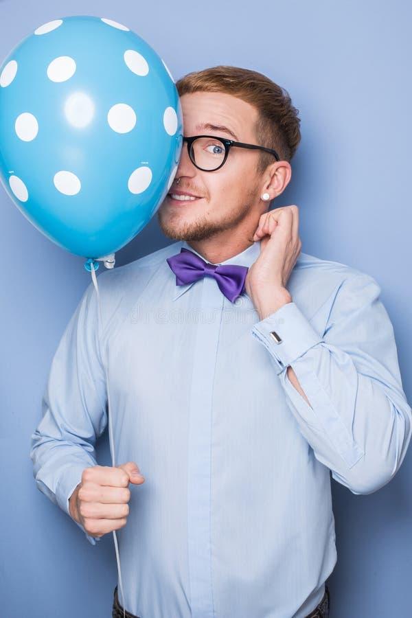 Giovane tipo con un pallone variopinto in sua mano Partito, compleanno, biglietto di S. Valentino fotografie stock libere da diritti